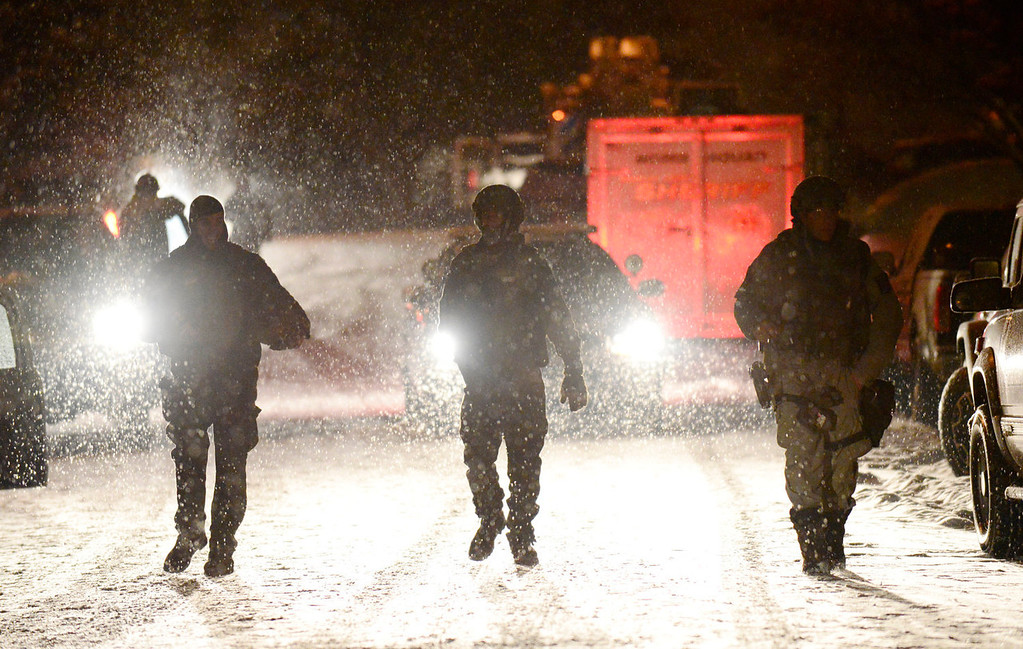 . Douglass County Sheriff\'s Office SWAT Team officers walk away from the scene of a shooting in the 500 block of Fox Hunt Circle in Highlands Ranch, Colorado, Friday, January 31, 2014. Officials on the scene confirmed two fatalities in the incident, which was reported around 7:30 p.m. (Photo By Brenden Neville / Special to The Denver Post)