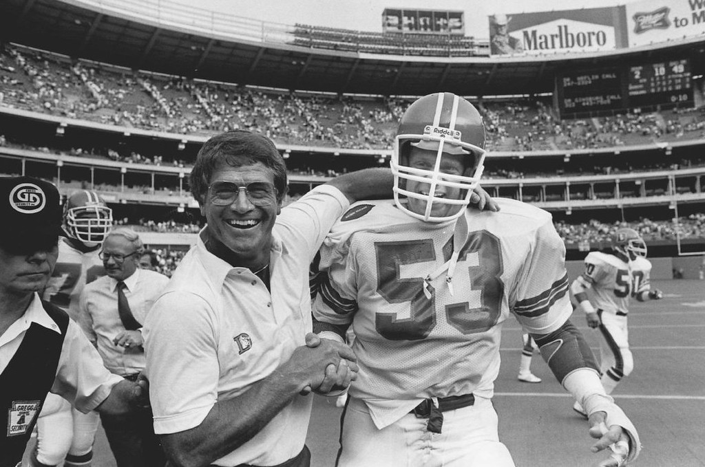 . A happy Dan Reeves gives a handshake and a hug to defensive star Randy Gradishar Sunday following the Denver Broncos\' 14-10 victory over the Pittsburgh Steelers at Three Rivers Stadium. Gradishar led a defense which got seven turnovers-three interceptions and four fumbles - and sacked Pittsburgh quarterback Cliff Stoudt four times. 1983.  (Photo by Jim Preston/The Denver Post)