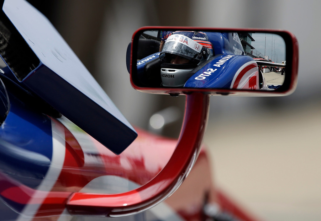 . Takuma Sato, of Japan, is reflected in the mirror of his car during a break in practice for the Indianapolis 500 auto race at the Indianapolis Motor Speedway in Indianapolis, Thursday, May 16, 2013. (AP Photo/Darron Cummings)