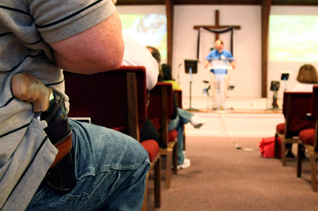 ". A man with a firearm listens to Pastor Ken Pagano during the ""Open Carry Celebration\"" at New Bethel Church in Louisville, Kentucky, June 27, 2009. Around 200 members of the church complied with a request asked to bring their unloaded handguns for a one-day celebration of the Second Amendment which stipulates the right to bear arms. REUTERS/Ed Reinke/Pool"