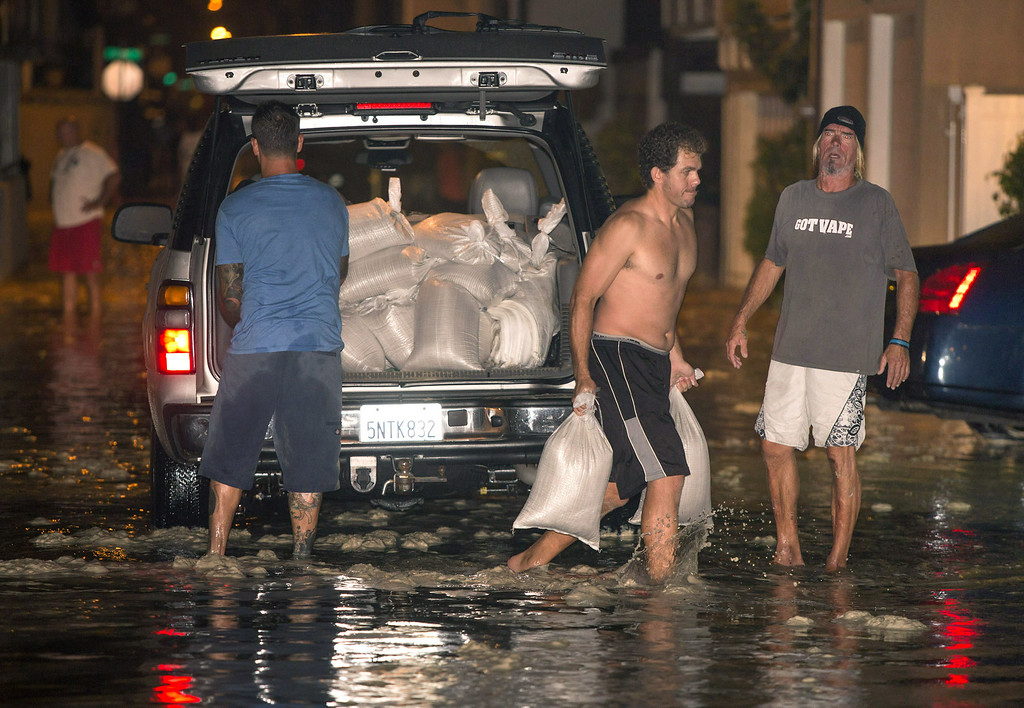 . In this Tuesday, Aug. 26, 2014 photo, residents carry sandbags to protect homes after high a tide and large waves caused heavy flooding in Seal Beach, Calif. A low-lying street in the Southern California coastal community of Seal Beach has been inundated by a surge of rising seawater brought on by Hurricane Marie spinning off Mexico\'s Pacific coast. (AP Photo/Kevin Warn)