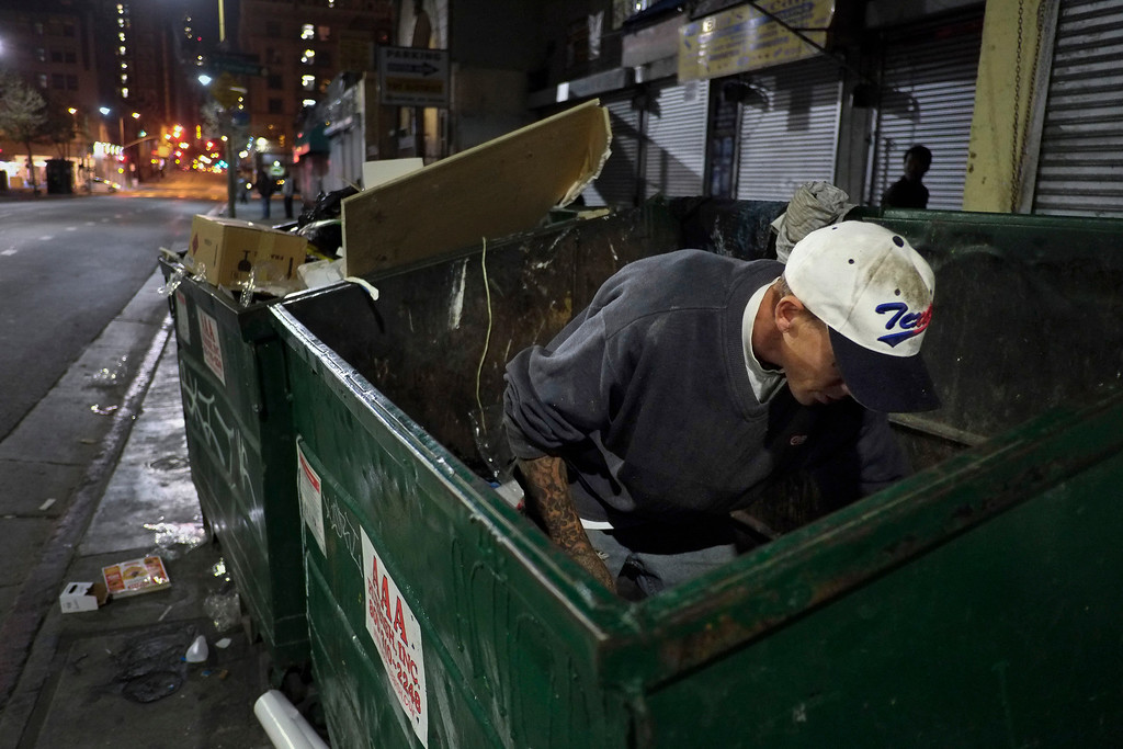 . Shawn McGray, a 34-year-old homeless man, looks through a dumpster for anything useful in the Skid Row area of Los Angeles, Thursday, March 21, 2013. McGray said his goal is to save enough money to move into a small apartment with his girlfriend. (AP Photo/Jae C. Hong)