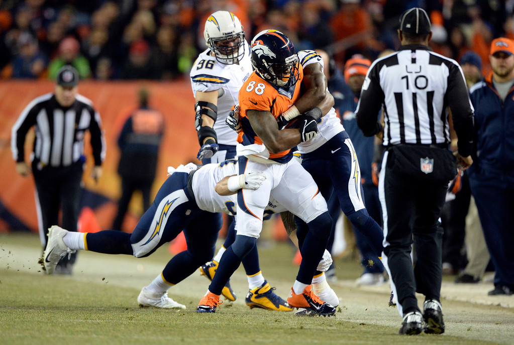 . Denver Broncos wide receiver Demaryius Thomas (88) gets wrapped up by Denver Broncos free safety Michael Huff (29) and San Diego Chargers inside linebacker Manti Te\'o (50) during the first half.  The Denver Broncos vs. the San Diego Chargers at Sports Authority Field at Mile High in Denver on December 12, 2013. (Photo by Hyoung Chang/The Denver Post)