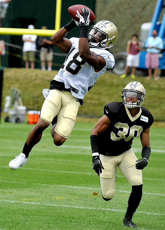 . New Orleans Saints wide receiver Charles Hawkins (18) catches the ball over defensive back Trevin Wade (30)  during NFL football training camp in White Sulphur Springs, W. Va., Sunday, July 27, 2014. (AP Photo/Chris Tilley)
