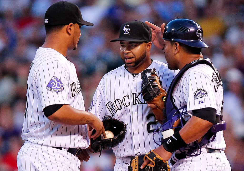 . Colorado Rockies\' Wilin Rosario, center, comes to the mound to meet with teammates Jhoulys Chacin, left, and catcher Yorvit Torrealba, right, for after committing his second error against the San Francisco Giants during the third inning of a baseball game, Wednesday, Aug. 28, 2013, in Denver. (AP Photo/Barry Gutierrez)