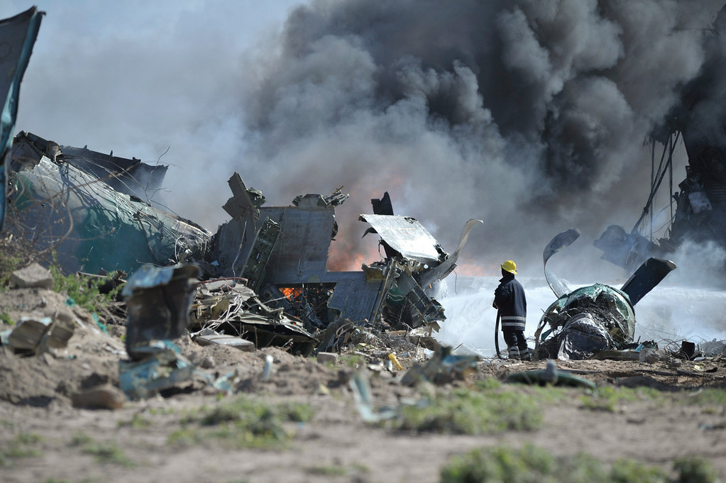 . In this handout photo released by African Union Mission in Somalia (AMISOM), AMISOM ,firefighters attempt to extinguish the fire at the site of an airplane crash in Mogadishu, Somalia, Friday, Aug. 9. 2013.  (AP Photo/Tobin Jones, AU/UN IST, AMISOM)