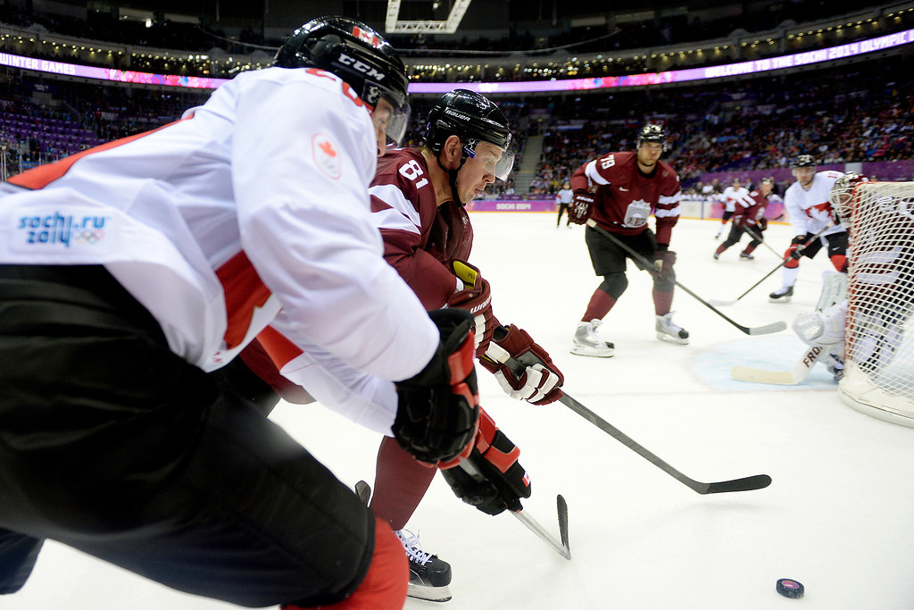 . SOCHI, RUSSIA - FEBRUARY 19: Georgijs Pujacs (81) of the Latvia and John Tavares (20) of the Canada vie for the puck during the first period of men\'s hockey action. Sochi 2014 Winter Olympics on Wednesday, February 19, 2014 at Bolshoy Ice Arena. (Photo by AAron Ontiveroz/ The Denver Post)