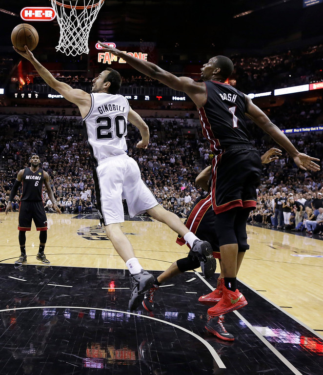. San Antonio Spurs guard Manu Ginobili (20) shoots as Miami Heat center Chris Bosh (1) defends during the first half in Game 5 of the NBA basketball finals on Sunday, June 15, 2014, in San Antonio. (AP Photo/David J. Phillip)