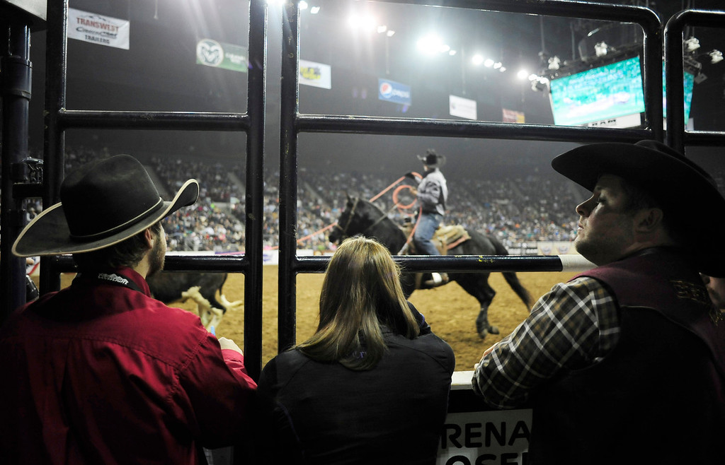 . From left, Cole Westfall, 21, of Limon, CO, Celie Vick, 17, of Byers, CO, and John Waite, 39, of Arvada, CO, watch a roping competition during the U.S. Bank Pro Rodeo Finals, at the National Western Stock Show in Denver, CO, Sunday, January 26, 2014. Sunday was the final day of the event.  (Photo By Brenden Neville / Special to The Denver Post)