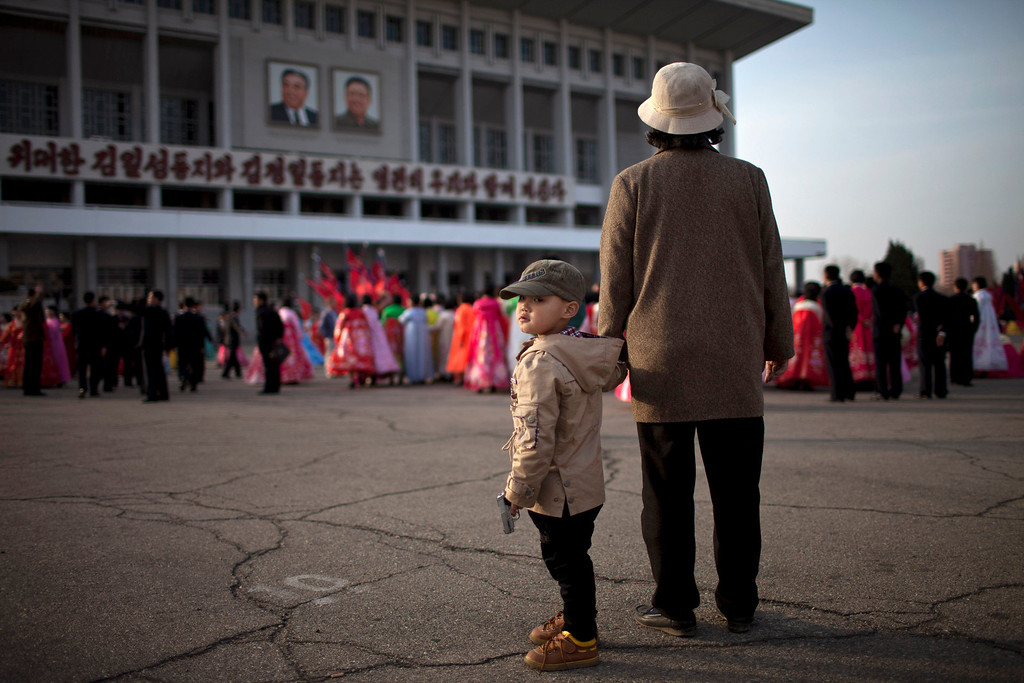 . A boy holds a toy gun while his grandmother watches a mass folk dance in front of the Pyongyang Indoor Stadium in Pyongyang, North Korea, Monday, April 15, 2013. Oblivious to international tensions over a possible North Korean missile launch, Pyongyang residents spilled into the streets Monday to celebrate a major national holiday, the birthday of their first leader, Kim Il Sung. (AP Photo/Alexander F. Yuan)