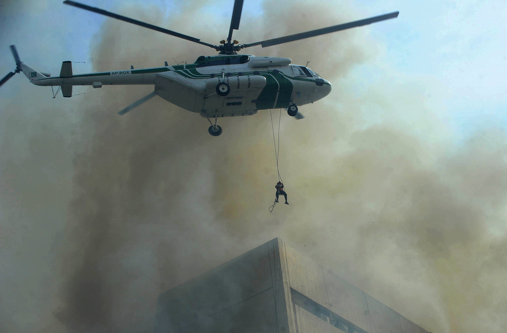. A Pakistani army helicopter rescues a man from a burning building in Lahore on May 9, 2013.  At least three persons fell from the 13-story LDA plaza situated on Lahore�s Edgerton road 9 trying to avoid a fire that engulfed the building.  AFP PHOTO/ Arif Ali/AFP/Getty Images