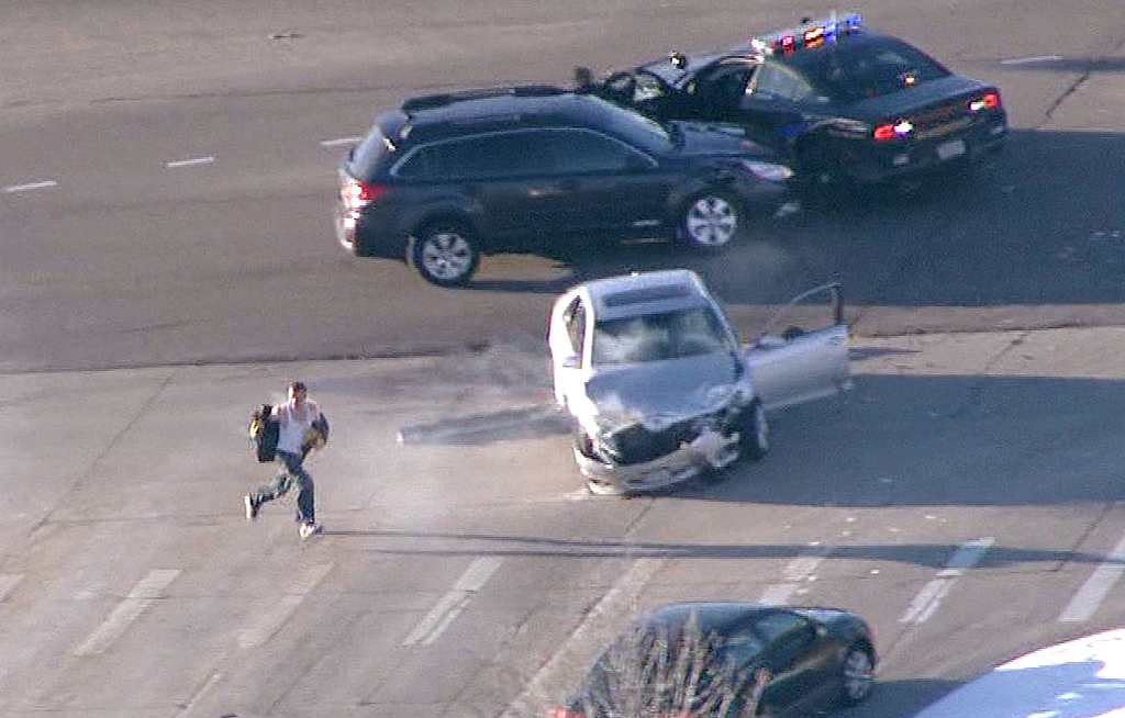 . In this image taken from video provided by CBS-4 TV Denver, Ryan Stone, 29, runs from a stolen (silver) car after causing a crash in Lone Tree, Colo., Wednesday, March 12, 2014. Stone, suspected of stealing an SUV with a 4-year-old boy inside, carjacking two other vehicles and seriously injuring a state trooper was arrested Wednesday after police tracked him, and at times chased him, around the Denver area during morning rush hour.  (AP Photo/CBS-4 TV Denver)