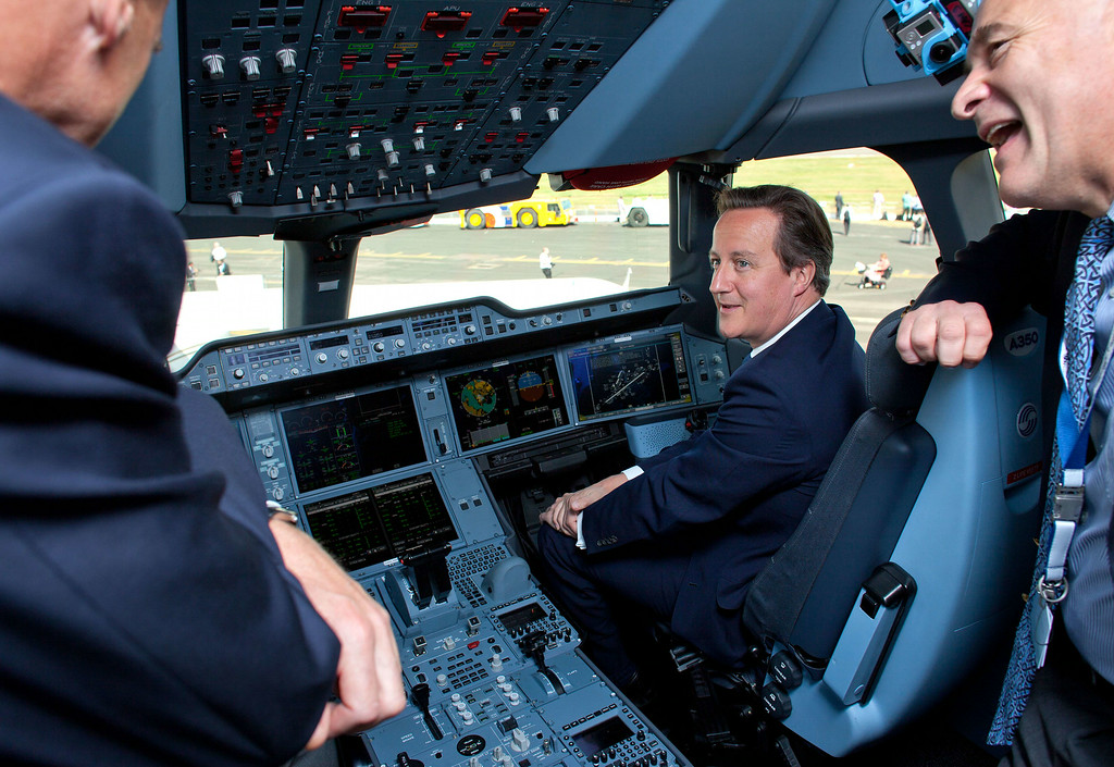 . British Prime Minister David Cameron (2nd R) is pictured as he sits in the cockpit of an Airbus A350 aircraft on the first day of the Farnborough International Airshow in southern England, on July 14, 2014. David Cameron on Monday announced an investment of £1.1 billion (1.38 billion euros, $1.88 billion) into the armed forces, the bulk of it on intelligence and surveillance equipment.  AFP PHOTO / BEN GURR/POOL/AFP/Getty Images