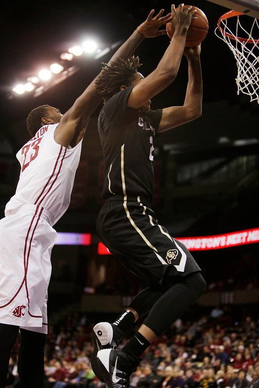 . Coloradoís Xavier Johnson, right, attempts a layup against Washington Stateís D.J. Shelton during the second half of an NCAA college basketball game Wednesday, Jan. 8, 2014, in Spokane, Wash. Colorado won 71-70 in overtime. (AP Photo/Young Kwak)