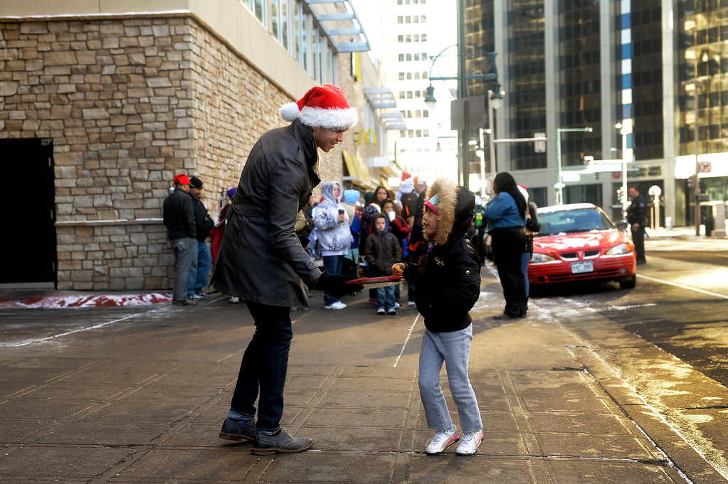 . A volunteer hands out cookies to people in need as they wait in line for the Father Woody Christmas Party to begin on Dec. 22 at the Sheraton Denver Downtown Hotel in Denver, Colo. Around 5,000 people attended the annual event, where a warm meal was served, gifts were handed out, and children could visit with Santa. Photo By Jamie Cotten, Special to The Denver Post