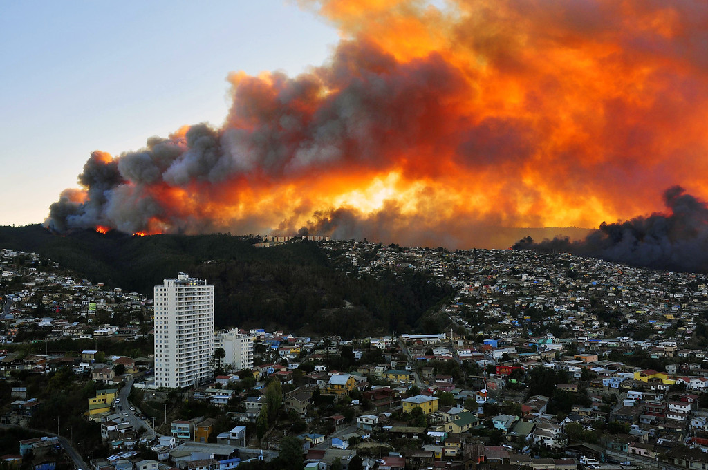 . View of houses in flames during a fire in Valparaiso, 110 km west of Santiago, Chile, on April 12, 2014. Authorities decreed a red alert for the area after the fire consumed more than 100 houses.   AFP PHOTO / ALBERTO MIRANDA