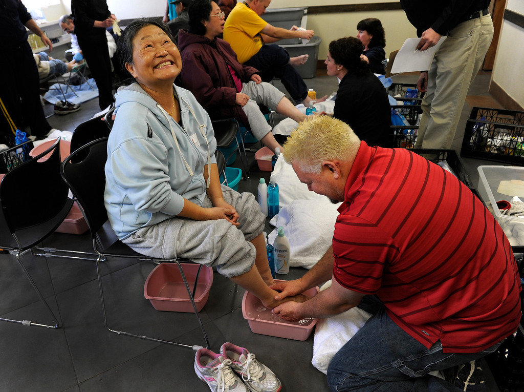 . DEVNER, CO.- MARCH 29: Myong Chang seems to enjoy the comfort provided by volunteer Joe Mudd, right, as he dips her feet in warm water. The Denver Rescue Mission partners with Volunteers of American and Runner\'s Roost to supply approximately 600 homeless adults and children with a new pair of shoes, sock and an Easter meal at the 20th Annual Easter Celebration  at the Rescue Mission on Lawrence Street. Many of the homeless had their feet washed by volunteers, symbolic of the part of the Christian tradition, mirroring Jesus\' washing of his disciples\' feet.(Photo By Kathryn Scott Osler/The Denver Post)