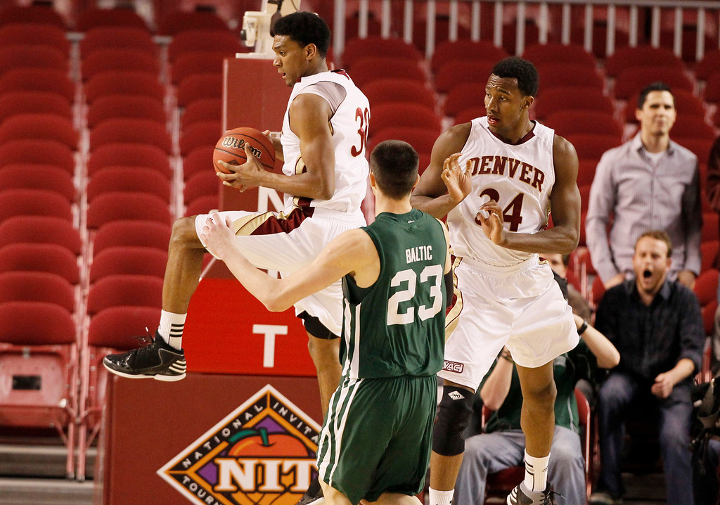 . Denver guard Cam Griffin, left, pulls in a rebound in front of Ohio forward Ivo Baltic, center, and Denver forward Chris Udofia in the second half of Denver\'s 61-57 victory in a first-round NIT college basketball game in Denver on Tuesday, March 19, 2013. (AP Photo/David Zalubowski)