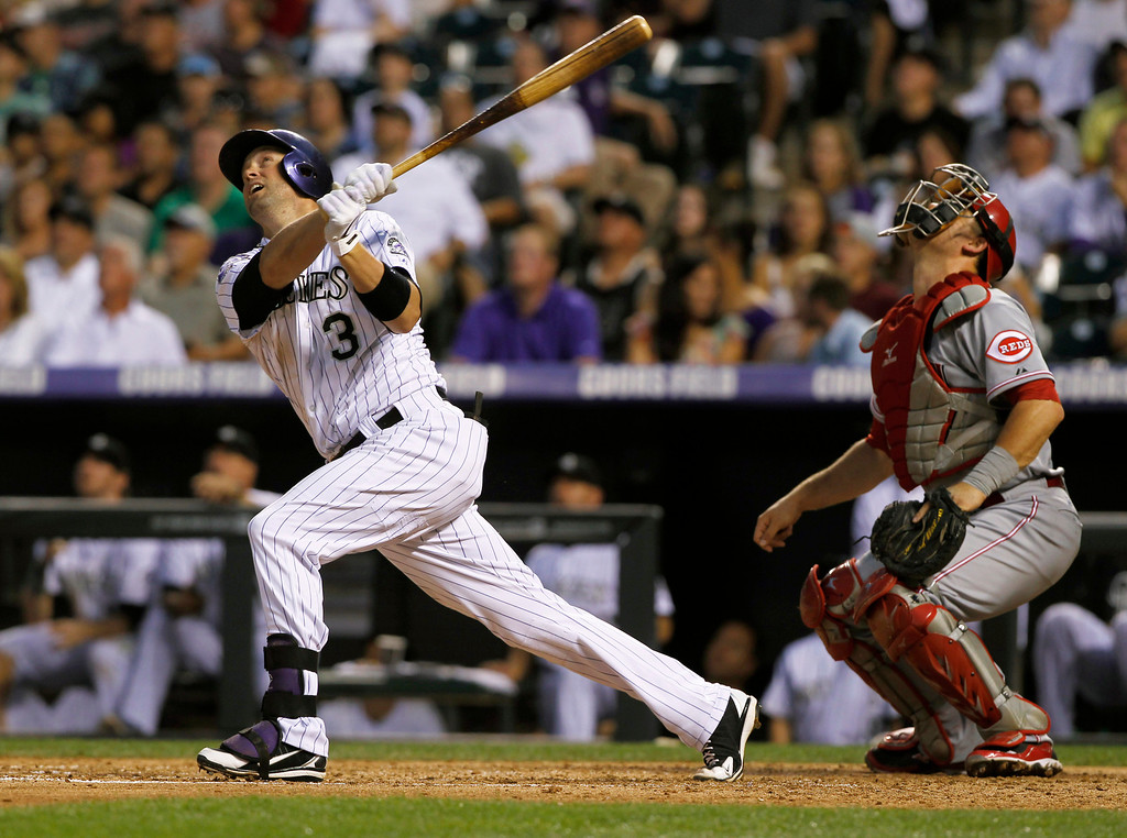 . Colorado Rockies\' Michael Cuddyer, left, follows the flight of his fly out with Cincinnati Reds catcher Devin Mesoraco in the fourth inning of a baseball game in Denver on Saturday, Aug. 31, 2013. (AP Photo/David Zalubowski)