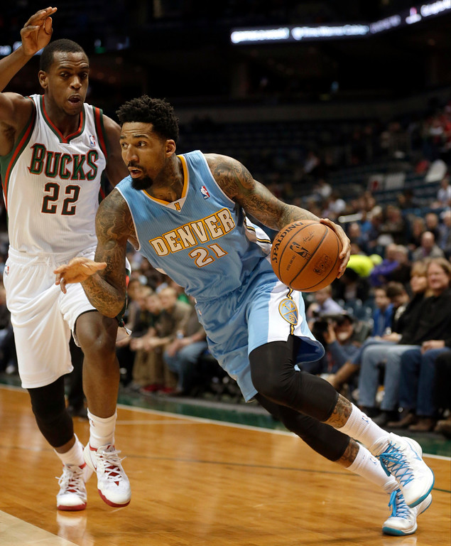 . Denver Nuggets\' Wilson Chandler (21) drives against Milwaukee Bucks\' Khris Middleton (22) during the first half of an NBA basketball game Thursday, Feb. 20, 2014, in Milwaukee. (AP Photo/Jeffrey Phelps)