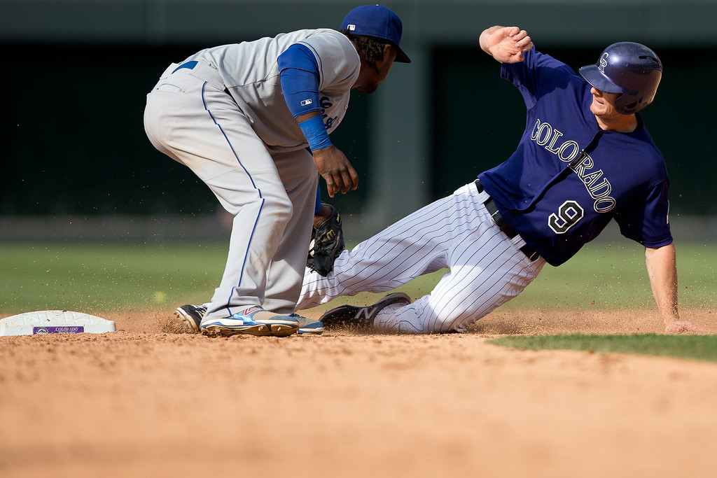 . DENVER, CO - JUNE 7:  DJ LeMahieu #9 of the Colorado Rockies is caught stealing at second base as shortstop Hanley Ramirez #13 of the Los Angeles Dodgers applies the tag for the second out of the ninth inning at Coors Field on June 7, 2014 in Denver, Colorado. The Rockies defeated the Dodgers 5-4 in 10 innings to end their eight game losing streak. (Photo by Justin Edmonds/Getty Images)