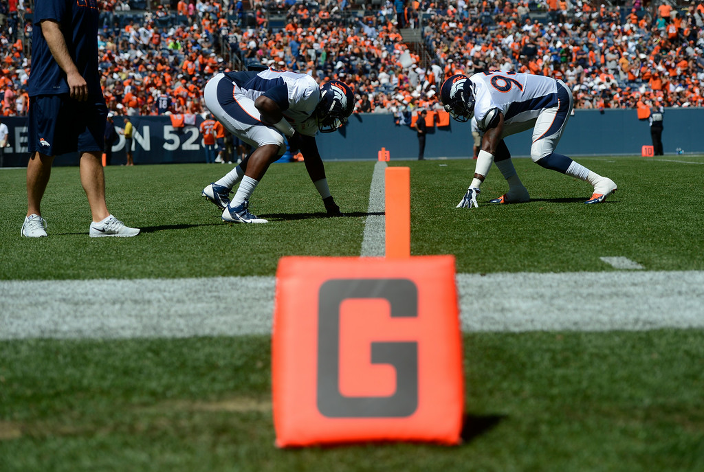 . Denver Broncos defensive ends, Kenny Anunike, left, and Quanterus Smith, right, line up against each other during practice at Sports Authority Field at Mile High Saturday afternoon, August 02, 2014. (Photo By Andy Cross / The Denver Post)