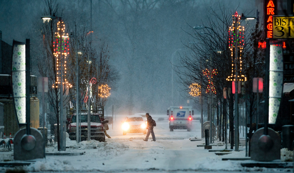 . A pedestrian crosses Fourth Street during a snow storm on Friday morning, Dec. 6, 2013, in downtown Columbus, Ind.  Several inches of snow fell on central and southern Indiana, making driving treacherous and leading to at least two fatal crashes. (AP Photo/The Republic, Andrew Laker)