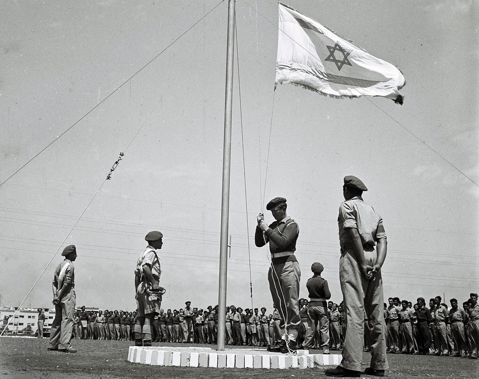 . PALESTINE - APRIL 27, 1948: Less than 3 weeks before Israel\'s independence, the flag of the future Jewish State is raised at morning parade at a training base of the fledgling Israeli Defense Forces April 27, 1948 in what was still the British Mandate for Palestine. (Photo by Zoltan Kluger/GPO via Getty Images)
