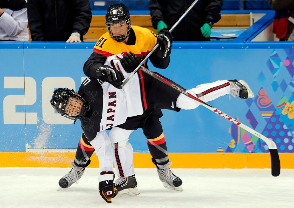 . Maritta Becker (R) of Germany fights for the puck with Japan player Ayaka Toko (L) during the match between Switzerland and Latvia at the Shayba Arena in the Ice Hockey tournament at the Sochi 2014 Olympic Games, Sochi, Russia.  EPA/ANATOLY MALTSEV