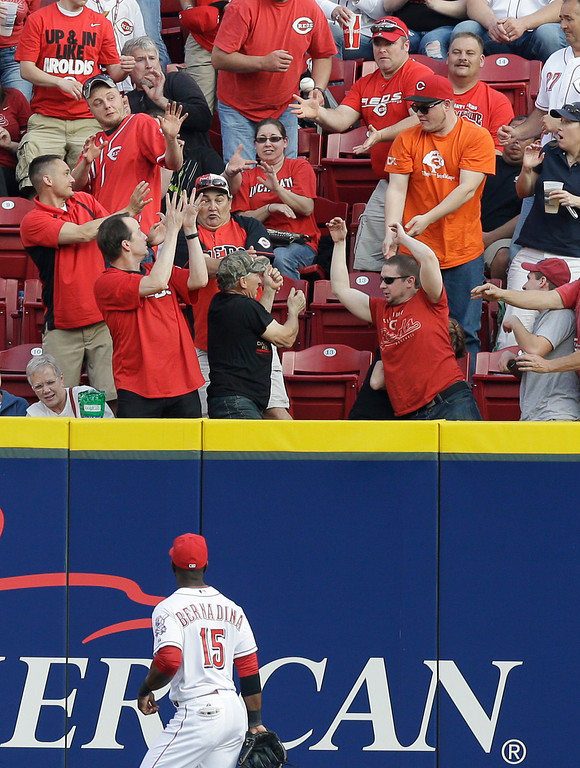 . Cincinnati Reds left fielder Roger Bernadina (15) watches a home run hit by Colorado Rockies\' Charlie Blackmon in the first inning of a baseball game on Saturday, May 10, 2014, in Cincinnati. (AP Photo/Al Behrman)