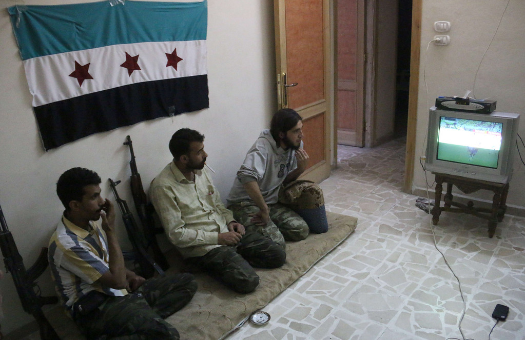 . Rebel fighters watch on television the opening World Cup 2014 football match between Brazil and Croatia on June 12, 2014 in the northern Syrian city of Aleppo. ZEIN AL-RIFAI/AFP/Getty Images