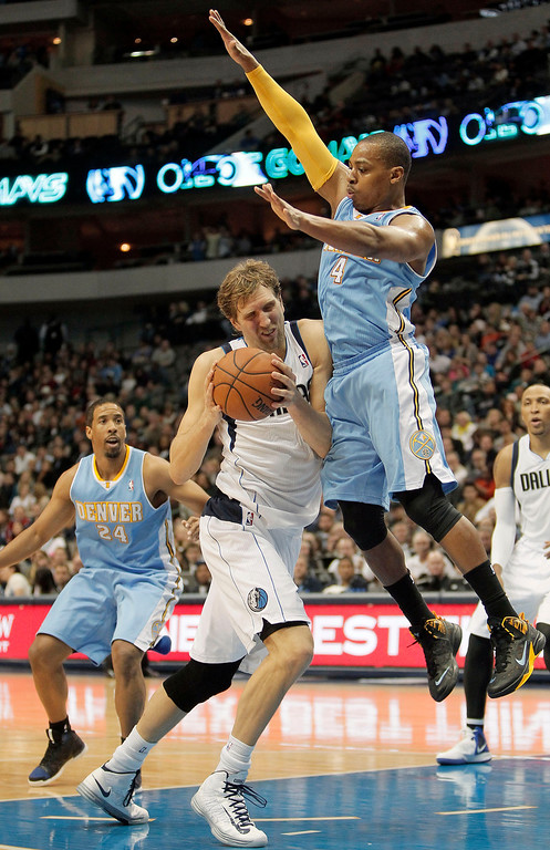 . Dallas Mavericks forward Dirk Nowitzki gets Denver Nuggets\' Randy Foye (4) off his feet during the second half of an NBA basketball game Monday, Nov. 25, 2013, in Dallas. Denver won 110-96. (AP Photo/Brandon Wade)