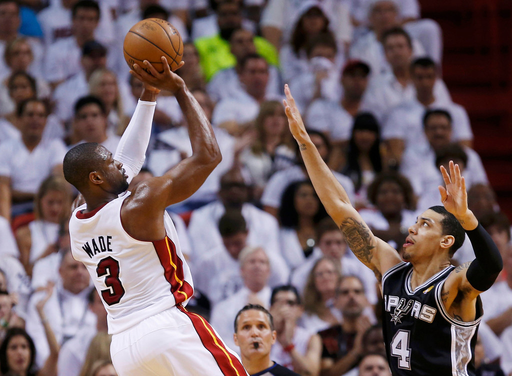 . Miami Heat\'s Dwyane Wade (L) shoots over San Antonio Spurs\' Danny Green during the second quarter in Game 7 of their NBA Finals basketball playoff in Miami, Florida June 20, 2013. REUTERS/Mike Segar