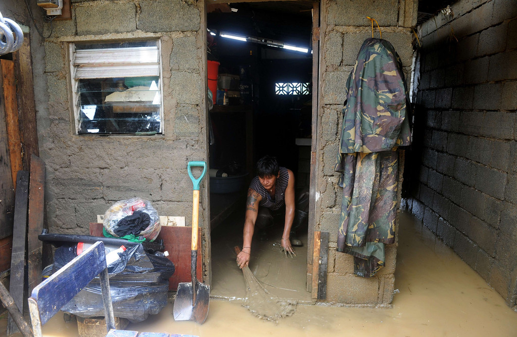 . Residents return to their houses to clean the mud brought by the floods in San Mateo, Rizal, east of Manila on August 22, 2013.  Disaster-weary Philippine residents mopped up on August 22 after four days of torrential rain that officials said had killed 17 people and forced more than half a million from flooded homes. NOEL CELIS/AFP/Getty Images