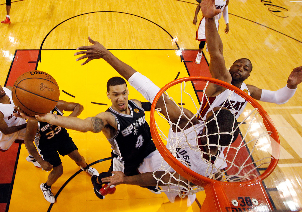 . San Antonio Spurs guard Danny Green (4) drives to the basket over Miami Heat center Chris Bosh (1) and  guard Dwyane Wade (3)during the first half in Game 3 of the NBA basketball finals, Tuesday, June 10, 2014, in Miami. (AP Photo/Wilfredo Lee)