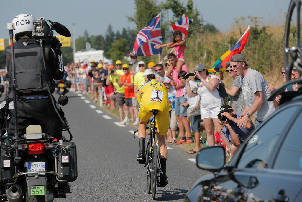 . Spectators, some with British flags, cheer as Christopher Froome of Britain, wearing the overall leader\'s yellow jersey, passes during the eleventh stage of the Tour de France cycling race, an individual time trial over 33 kilometers (20.6 miles) with start in in Avranches and finish in Mont-Saint-Michel, western France, Wednesday July 10 2013. (AP Photo/Christophe Ena)