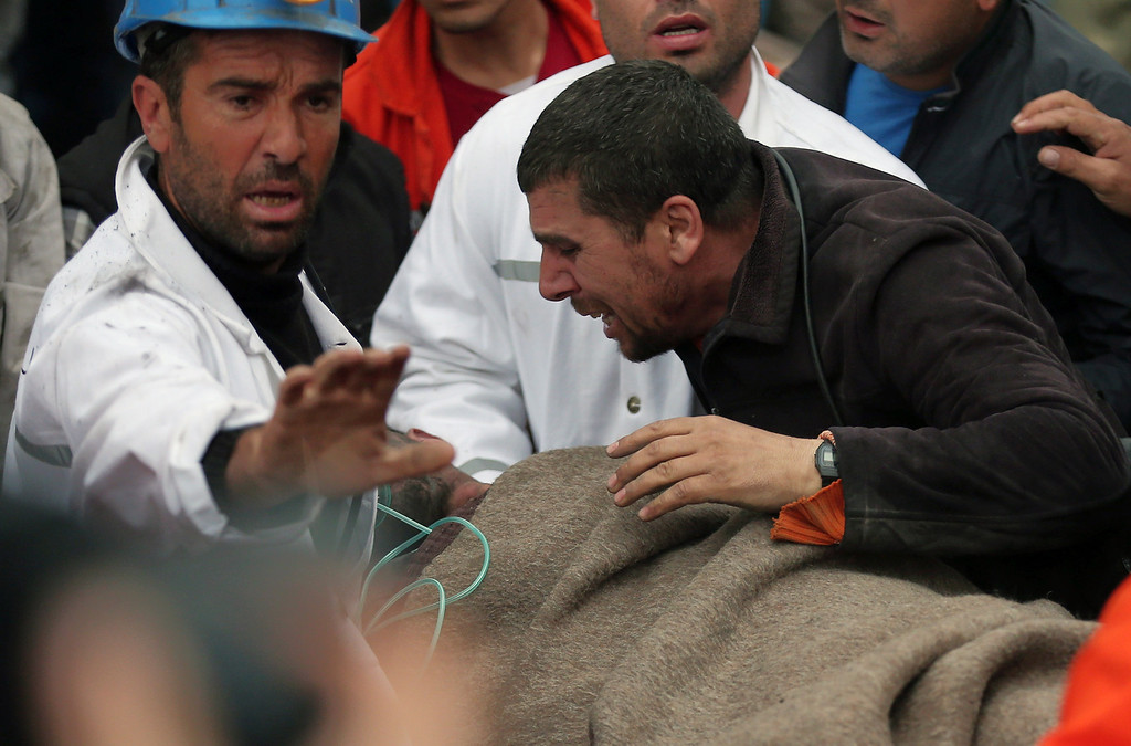 . A man reacts as rescue workers carry the body of a miner from the mine in Soma, western Turkey, early Wednesday, May 14, 2014. (AP Photo/Emrah Gurel)