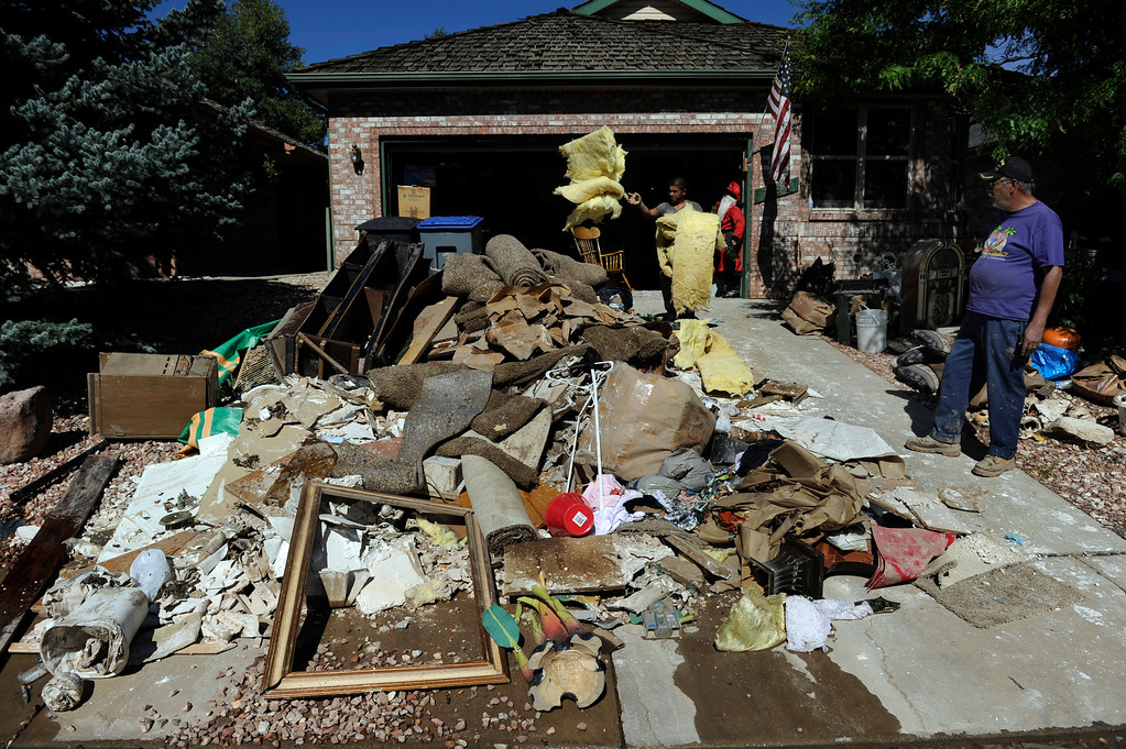 . LONGMONT, CO - Sept. 20: Luis Vega, right,  stands in front of his rental property while a small crew that he hired removes items from the basement of the home. Residents along Wade Rd. just south of the Twin Peaks Golf Course continue the cleanup after floods last week devastated the neighborhood. (Photo By Kathryn Scott Osler/The Denver Post)
