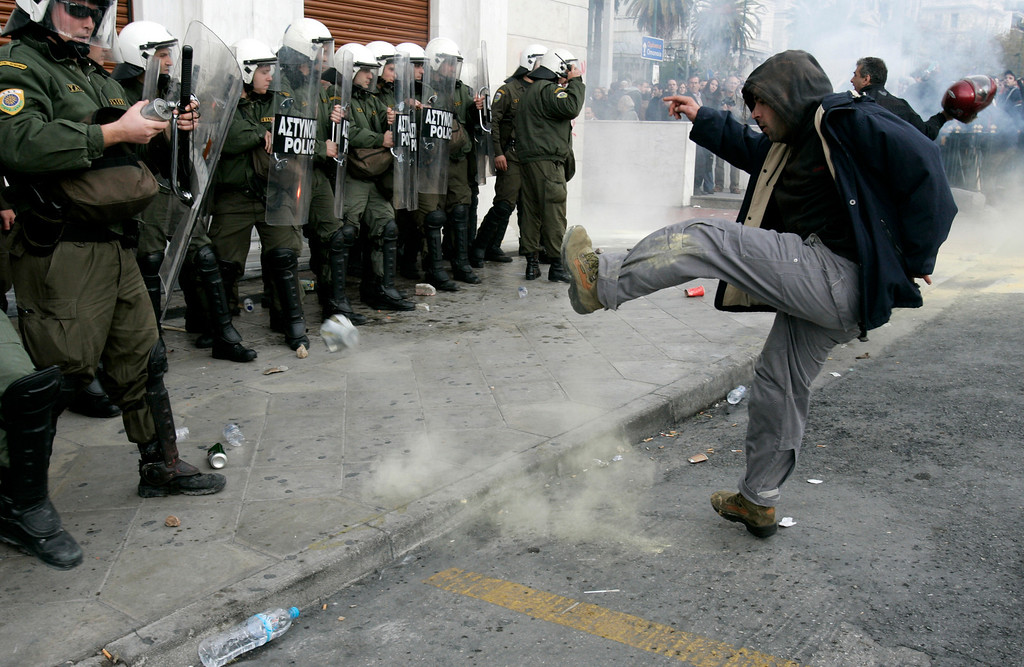 . A protester kicks a tear gas canister back at policemen during a during a mass rally in Athens December 12, 2007. Striking workers brought Greece to a standstill  and tens of thousands marched through the streets of Athens to protest against the government\'s pension reform plans.  REUTERS/Yiorgos Karahalis