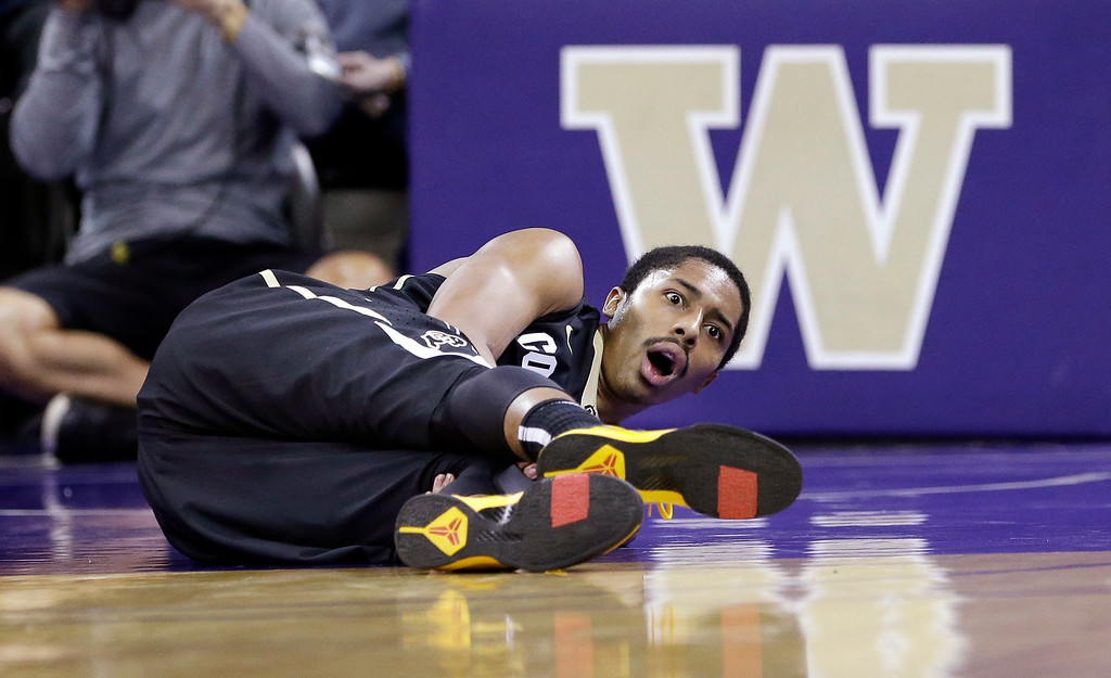 . Colorado\'s Spencer Dinwiddie looks up after falling to the court against Washington with an injury in the first half of an NCAA college basketball game, Sunday, Jan. 12, 2014, in Seattle. (AP Photo/Elaine Thompson)