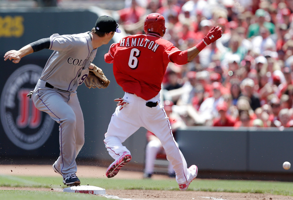 . Cincinnati Reds\' Billy Hamilton (6) is safe at first with a bunt single as Colorado Rockies second baseman DJ LeMahieu (9) watches the throw from Justin Morneau go by in the first inning of a baseball game, Sunday, May 11, 2014, in Cincinnati. Morneau was given an error on the throw that allowed Hamilton to reach third. (AP Photo/Al Behrman)