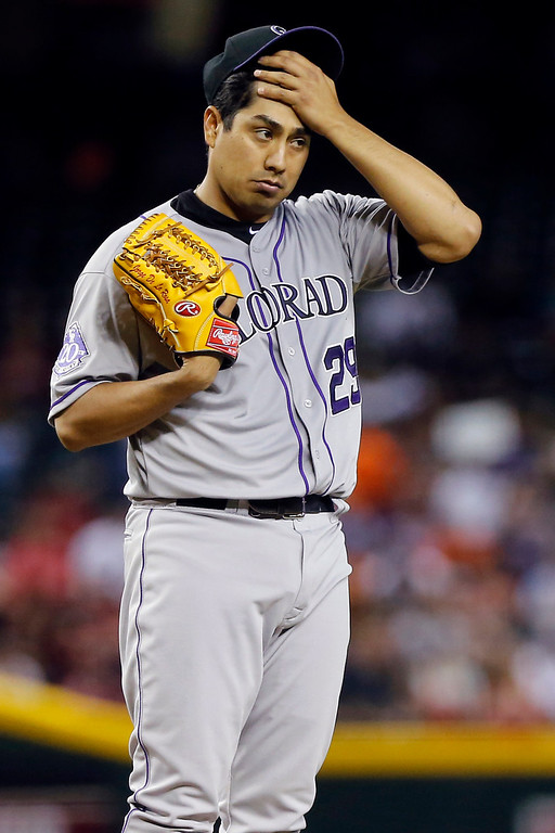 . Colorado Rockies pitcher Jorge De La Rosa wipes his head during the fifth inning of a baseball game against the Arizona Diamondbacks, Thursday, April 25, 2013, in Phoenix. (AP Photo/Matt York)