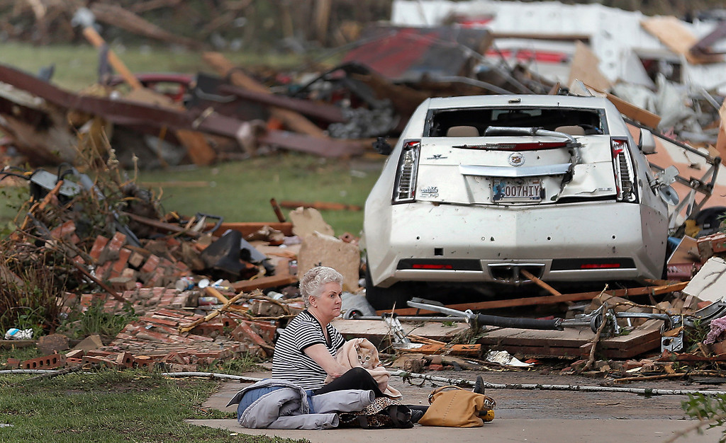 . Kay James holds her cat as she sits in her driveway after her home was destroyed by the tornado that hit the area on Monday, May 20, 2013 in Oklahoma City, Okla. (AP Photo/The Oklahoman, Chris Landsberger)
