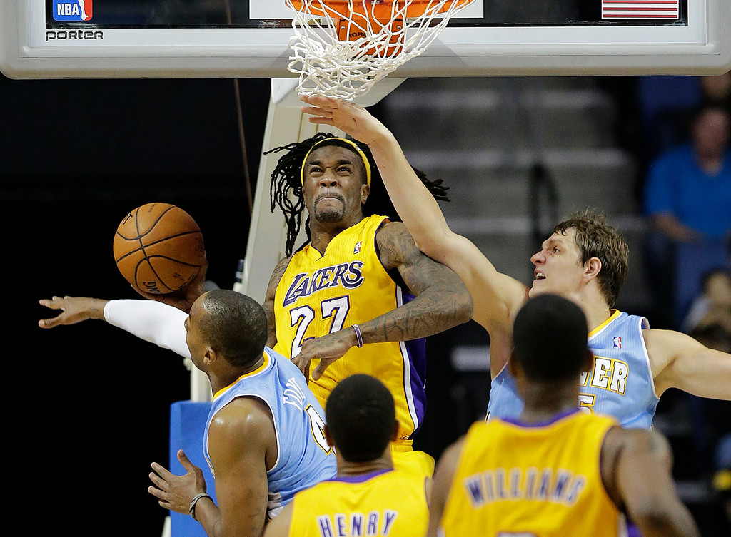 . Los Angeles Lakers\' Jordan Hill, center, goes up for a basket against Denver Nuggets\' Randy Foye, left, and Timofey Mozgov, right, of Russia, in the second half of an NBA preseason basketball game on Tuesday, Oct. 8, 2013, in Ontario, Calif. The Lakers won 90-88. (AP Photo/Jae C. Hong)