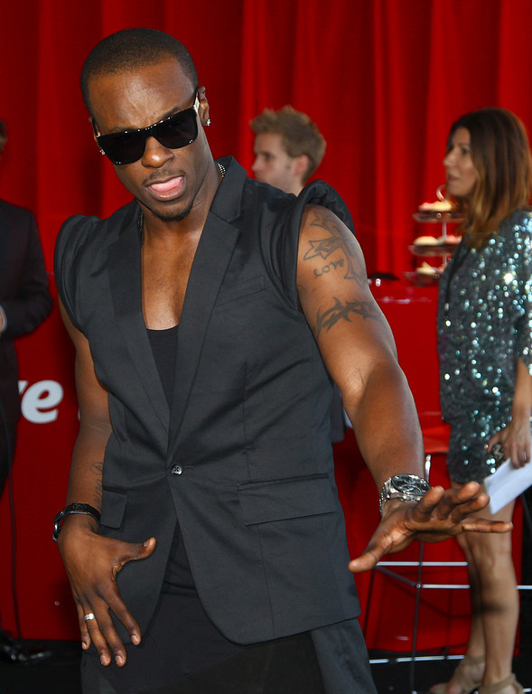 . Tim Omaji, better known by his stage name Timomatic, arrives for the Australian music industry Aria Awards in Sydney, Thursday, Nov. 29, 2012. (AP Photo/Rick Rycroft)