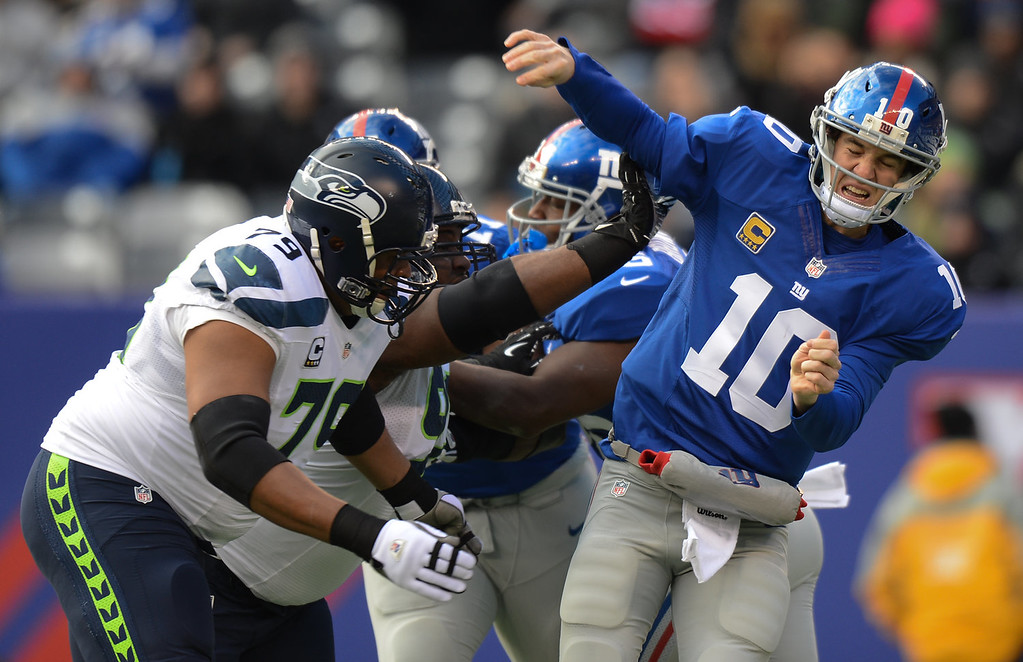 . Quarterback Eli Manning #10 of the New York Giants is hit as he throws a pass in the 1st half  against the Seattle Seahawks at MetLife Stadium on December 15, 2013 in East Rutherford, New Jersey. (Photo by Ron Antonelli/Getty Images)