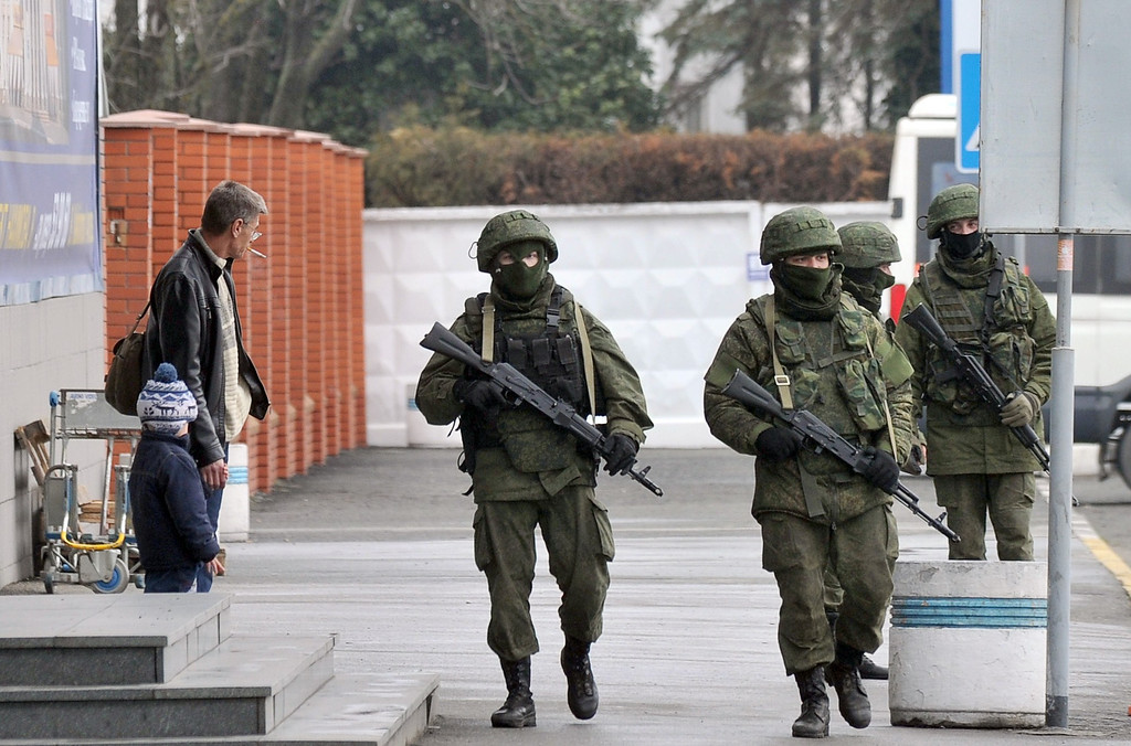 ". Unidentified armed men patrol outside of Simferopol airport on February 28, 2014. Ukraine accused today Russia of staging an ""armed invasion\"" of Crimea and appealed to the West to guarantee its territorial integrity after pro-Moscow gunmen took control of the peninsula\'s main airport.   AFP PHOTO/ GENYA SAVILOV/AFP/Getty Images"