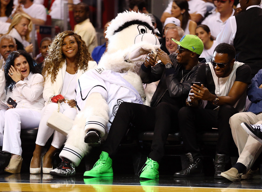 . MIAMI, FL - JUNE 12:  Tennis player Serena Williams (L) and runner Usain Bolt (R) meet with Miami Heat mascot Burnie during Game Four of the 2014 NBA Finals between the Miami Heat and the San Antonio Spurs at American Airlines Arena on June 12, 2014 in Miami, Florida. (Photo by Andy Lyons/Getty Images)