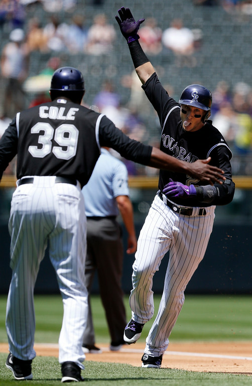 . Colorado Rockies\' Troy Tulowitzki (2) celebrates a solo home run with third base coach Stu Cole (39) during the first inning of a baseball game against the San Diego Padres on Wednesday, July 9, 2014, in Denver. (AP Photo/Jack Dempsey)