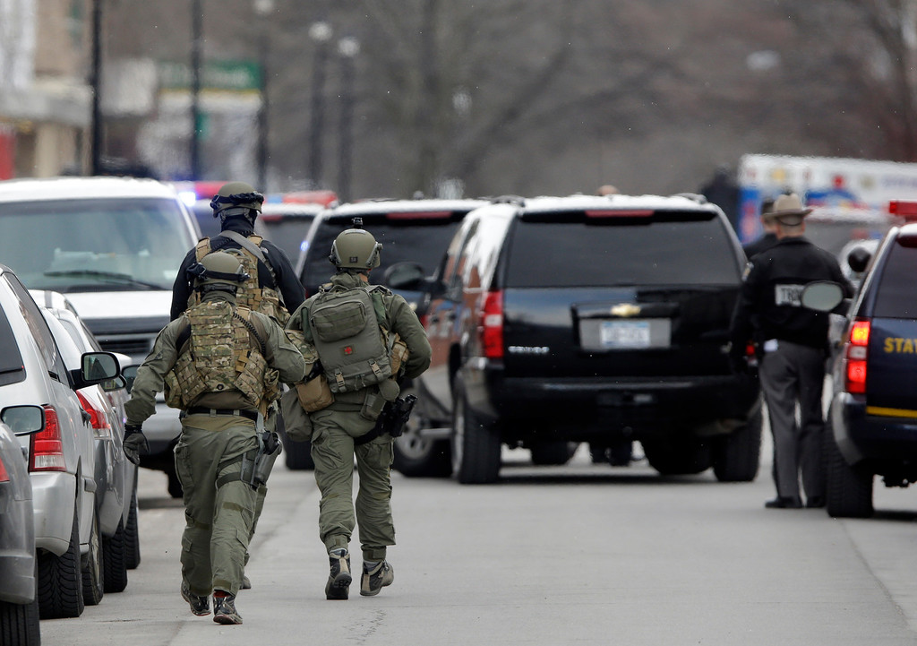 . Police walk along Main Street in Herkimer, N.Y., as they search for a suspect in two shootings that killed four and injured at least two on, Wednesday, March 13, 2013.  (AP Photo/Mike Groll)